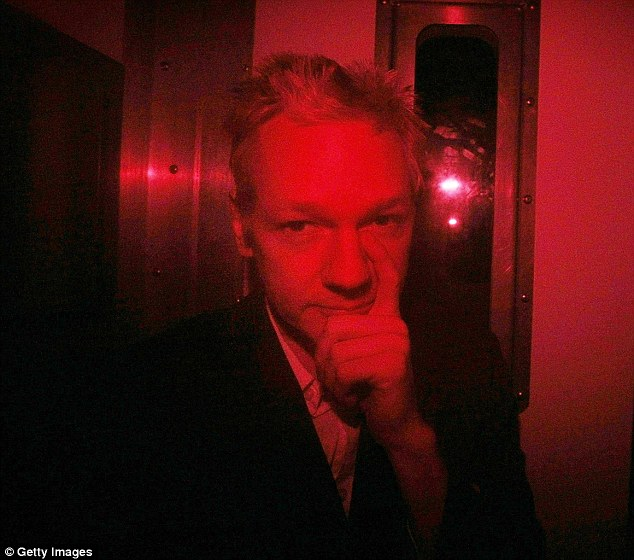Julian Assange tapping his nose from inside a prison van