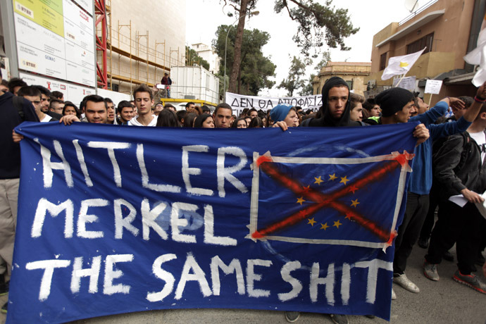 Cypriot college students hold a banner comparing German Chancellor Angela Merkel to Nazi dictator Adolf Hitler during a protest in Nicosia against a bailout for the financially crippled island on March 26, 2013. Cyprus secured a deal with the troika for a 10-billion-euro ($13 billion) bailout that helped it avert bankruptcy but which will see large deposit-holders at its two biggest banks losing much of their savings. AFP PHOTO/PATRICK BAZ
